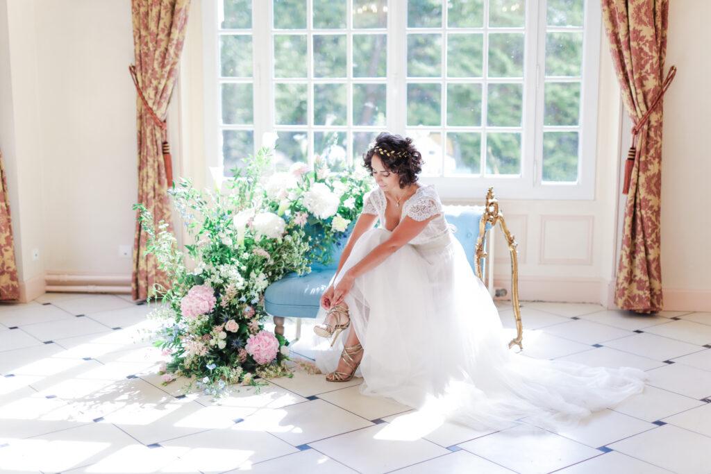 mariée qui enfile sa chaussure sur un canapée bleu
