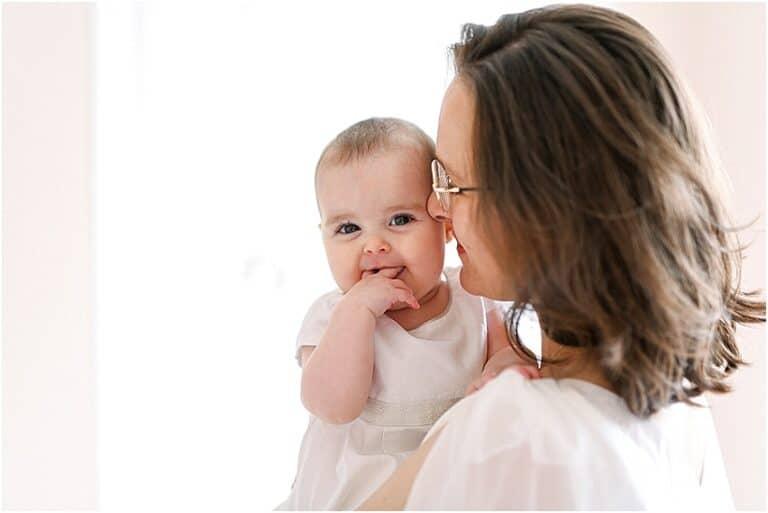 bébé qui sourit dans les bras de sa maman