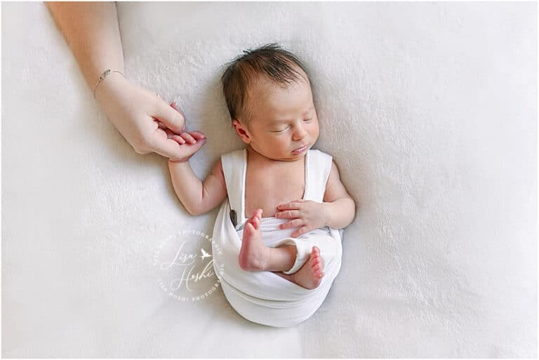 bébé tenant la main de sa maman