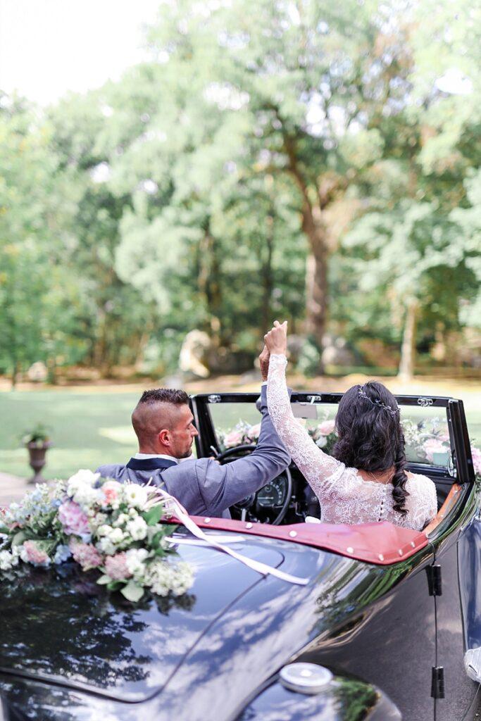 mariés dans une voiture décapotable noir de dos